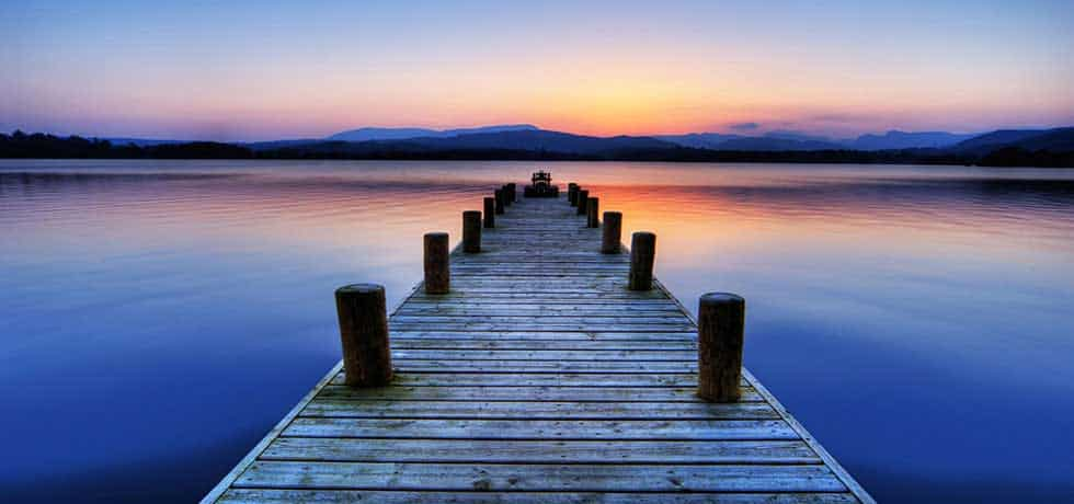 Dock extending into water with sunset behind mountains