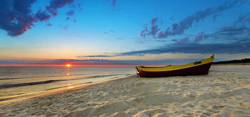 Boat on beach at sunset