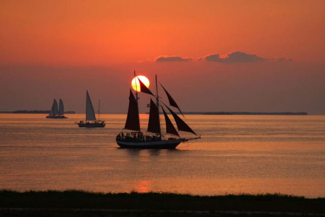 Three sailboats on water with orange sunset behind