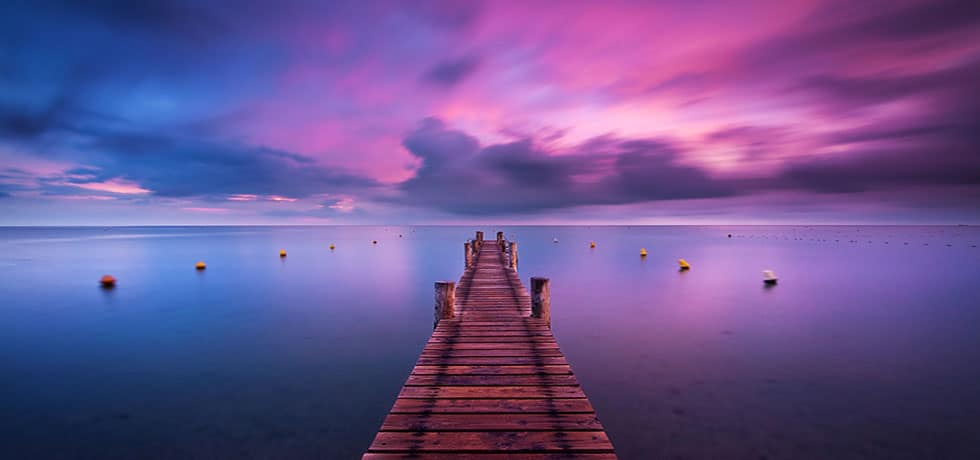 Dock extending into water with bluish/purple sunset